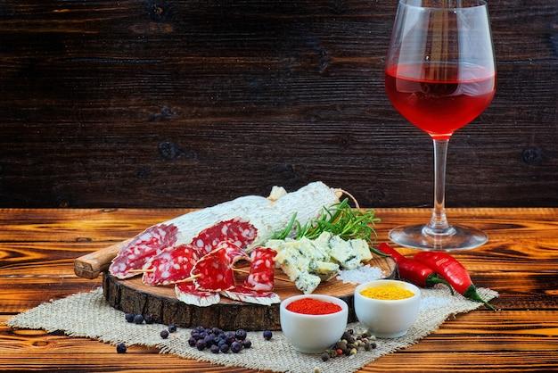 Salsiccia stagionata affettata con spezie e un bicchiere di vino rosso su fondo rustico in legno scuro.