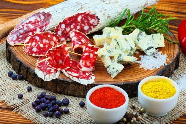 Salsiccia stagionata affettata con spezie e un rametto di rosmarino su fondo rustico in legno scuro.