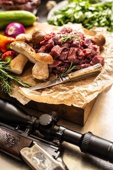 Carne di cervo affettata preparata per stufato di selvaggina funghi erbe verdure coltello e pistola cacciatore.