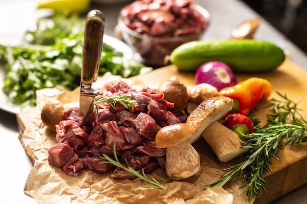 Carne di cervo affettata preparata per stufato di selvaggina funghi di bosco erbe verdure e coltello.