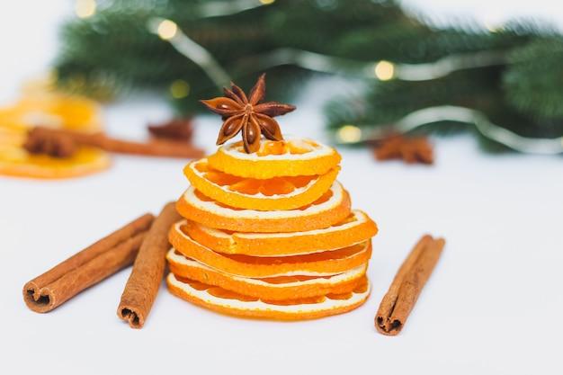 Fette di arancia secca con rami di pino natalizio e spezie