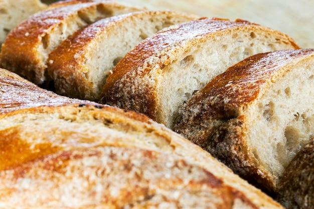 Fette di pane aromatizzato fresco, pezzi di polpa di pane morbido su un tagliere, primo piano