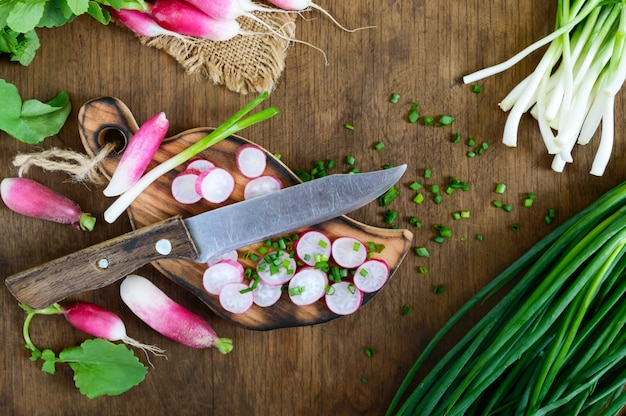 Ravanelli rossi freschi affettati e giovani cipolle verdi su fondo di legno bianco. dieta sana con ravanello. ingredienti per un'insalata di verdure primaverile leggera. la vista dall'alto