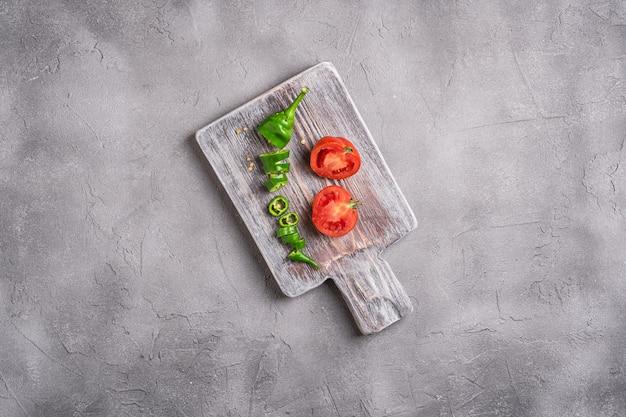 Pomodori maturi freschi affettati con peperoncino piccante sul vecchio tagliere di legno