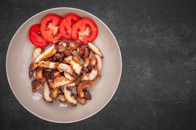 Maiale fritto affettato con pomodoro in piatto ceramico marrone su fondo di struttura di tono scuro con lo spazio della copia per testo, vista superiore