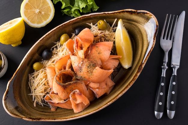 Stroganina di salmone crudo congelato affettato su un piatto con formaggio, olive e limone. pesce surgelato a fette. vista dall'alto. avvicinamento