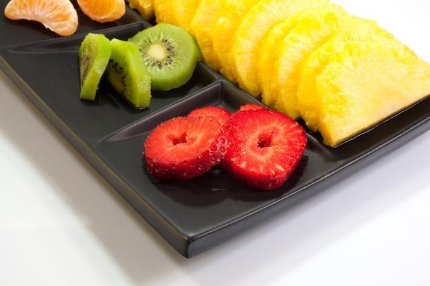 Frutta a fette su piattino nero