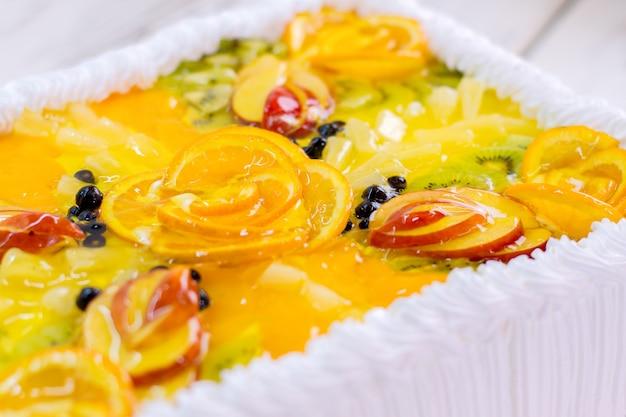 Frutta a fette in gelatina. dessert colorato con decorazione. torta gustosa con crema al burro. prodotto dolciario del negozio.