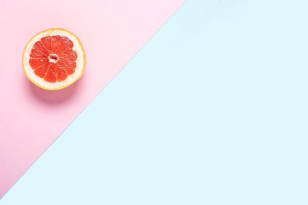 Pompelmo a fette su sfondo rosa e blu.