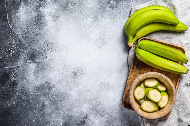 Banana verde affettata in una ciotola di legno. sfondo grigio. vista dall'alto. spazio per il testo. frutta tropicale