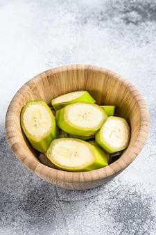 Banana verde affettata in una ciotola di legno. sfondo grigio. vista dall'alto. frutta tropicale