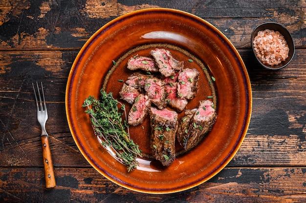 Fette di bistecche di petto barbecue alla griglia fette su un piatto rustico