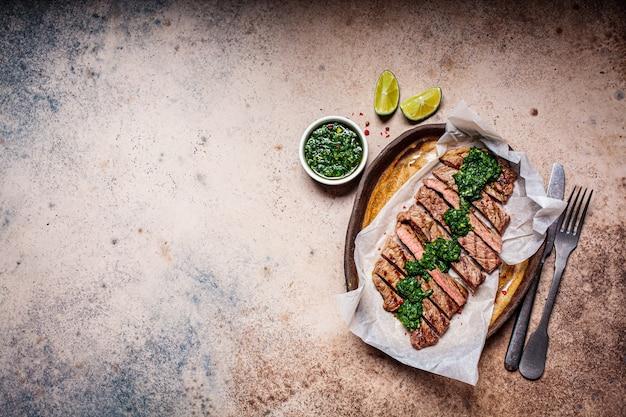 Fette di bistecca di manzo alla griglia con salsa chimichurri sul piatto scuro, vista dall'alto, sfondo scuro.