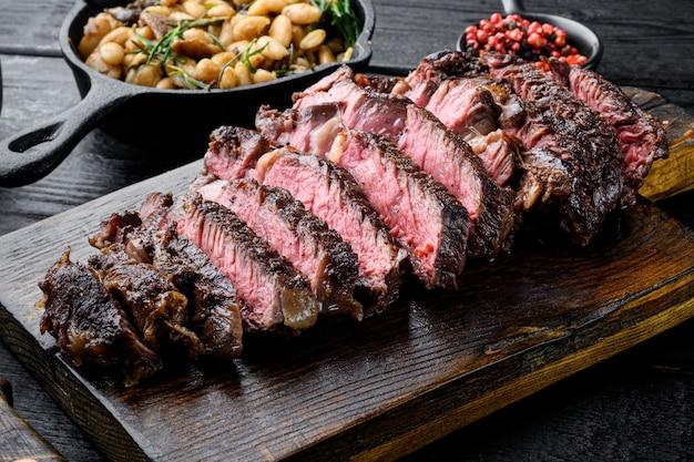 Fette di carne alla griglia bistecca rib eye set medio raro, sul tagliere di legno, con fagioli bianchi e rosmarino in padella di ghisa, sul tavolo di legno nero