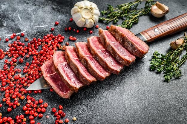 Bistecca alla griglia superiore affettata. carne di manzo biologica su fondo nero. vista dall'alto