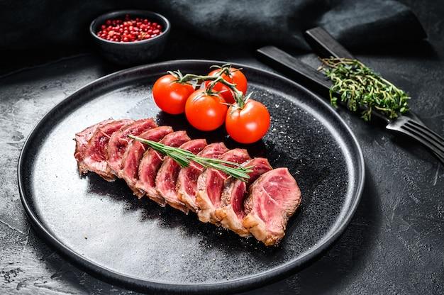 Bistecca alla griglia superiore affettata su un piatto. carne di manzo biologica su fondo nero. vista dall'alto