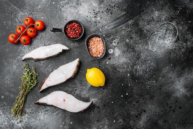 Set di pesce halibut affettato, con ingredienti ed erbe di rosmarino, su sfondo nero tavolo in pietra scura, vista dall'alto piatta, con copia spazio per il testo