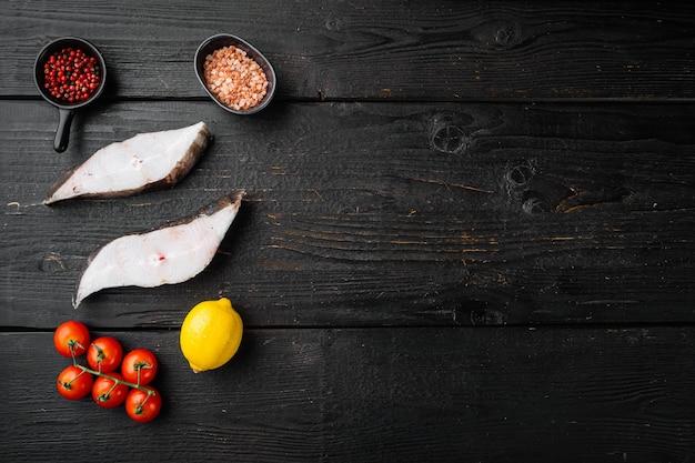 Set di pesce halibut affettato, con ingredienti ed erbe di rosmarino, su sfondo tavolo in legno nero, vista dall'alto piatta, con copia spazio per il testo
