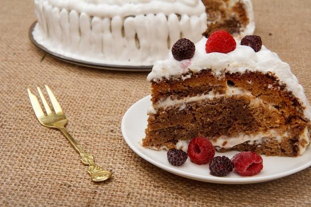 Torta a fette biscottata fatta in casa decorata con panna montata e una forchetta sul tavolo con tela di sacco.