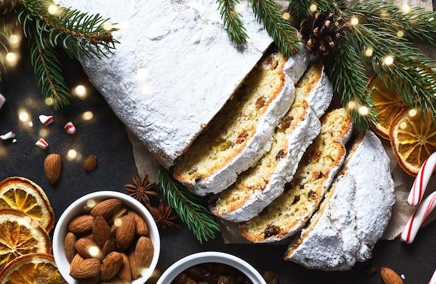 Fette di dolci natalizi fatti in casa stollen con uvetta e noci sul tavolo rustico con cannella. rami di albero di natale, fuoco selettivo