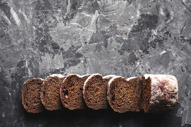 Pane di frumento bianco casalingo affettato con farina di frumento sulla vecchia teglia da forno nera come sfondo. vista dall'alto