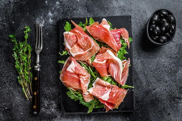 Fette di prosciutto di maiale serrano jamon carne su una tavola di marmo. sfondo nero. vista dall'alto.