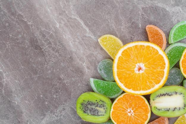 Fette di succosa frutta fresca con caramelle colorate sulla superficie in marmo.