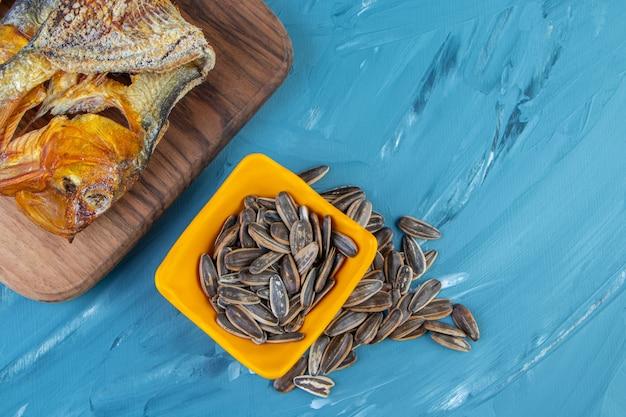 Fette di limone, chips di pane e pesce essiccato su un tagliere, sullo sfondo blu.