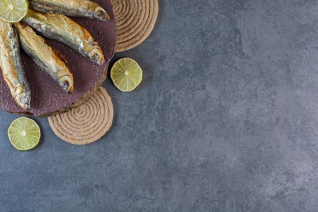 Limoni a fette e pesce salato essiccato su una tavola su un sottopentola, sullo sfondo di marmo.