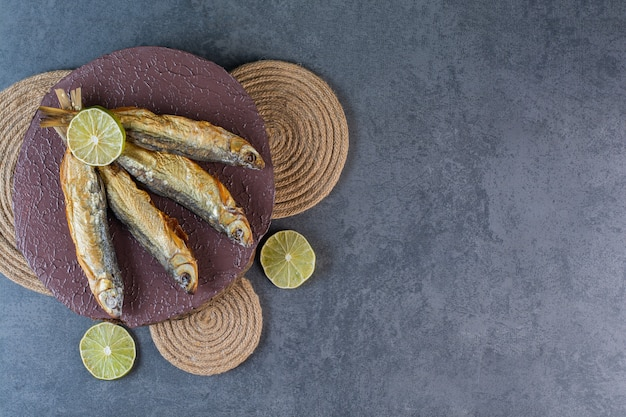 Limoni a fette e pesce salato essiccato su una tavola su un sottopentola, sulla superficie del marmo