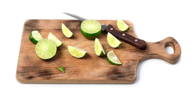 Calce e coltello a fette sul tagliere di legno isolato