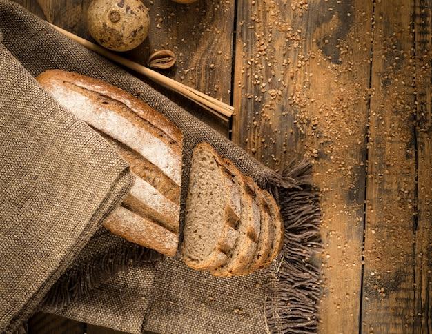 Pagnotta di pane a fette su un tovagliolo di stoffa su una superficie di legno, vista dall'alto