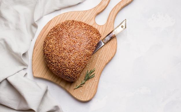 Pagnotta di pane bianco a fette con semi di sesamo su una tavola di legno. copia spazio