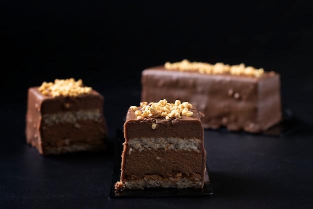 Dessert di mousse a fette con pralina di nocciole, cioccolato al latte e glassa gourmet ricoperta di cioccolato e noci su fondo nero.