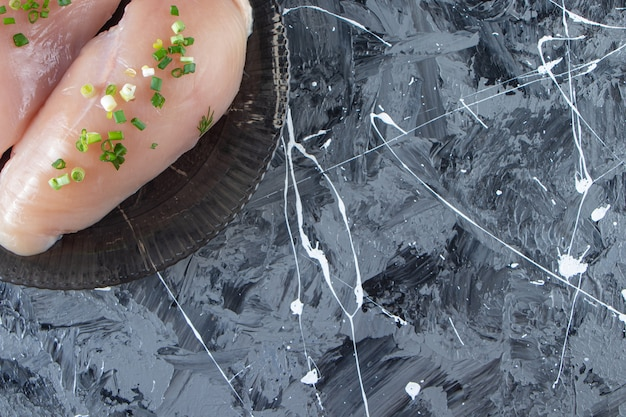 Cipolla affettata e petto di pollo su un piatto, sullo sfondo di marmo.