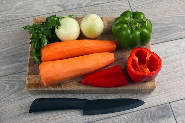 Tagliata di cipolla e pepe su un tagliere da cucina con prezzemolo e carote