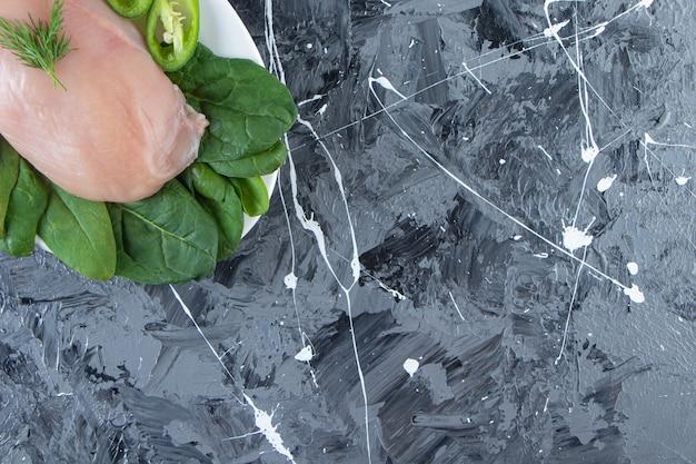 Pepe a fette, spinaci e petto di pollo su un piatto, sullo sfondo di marmo.