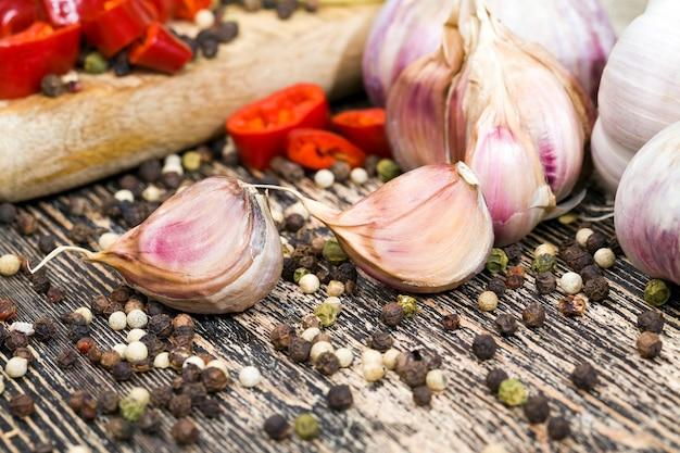 Fette di aglio amaro maturo e altre verdure, tavolo da cucina durante la cottura degli alimenti, primo piano