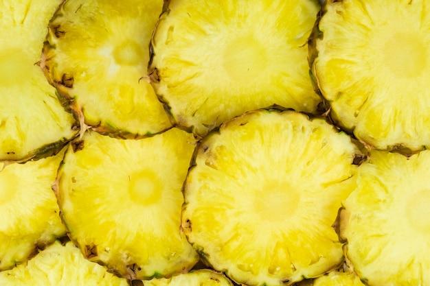 I pezzi di ananas a fette giacevano nel modello, vista dall'alto. la frutta dell'ananas appena tagliata giaceva l'una sull'altra