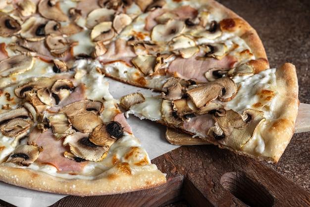 Pizza a fette con prosciutto e funghi, pizza con crosta sottile fatta in casa sulla tavola di legno, fuoco selettivo