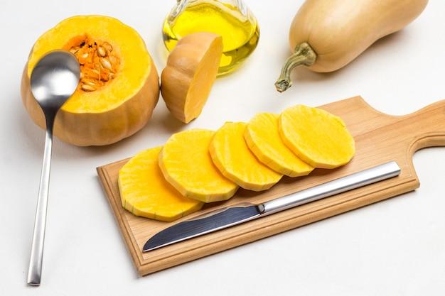 Zucca affettata e coltello sul tagliere. zucca con semi e cucchiaio. bottiglia di olio e zucca intera. vista dall'alto. sfondo bianco