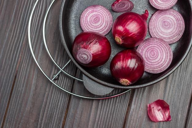 Cipolle viola affettate in padella. bucce sul tavolo. fondo in legno scuro. vista dall'alto
