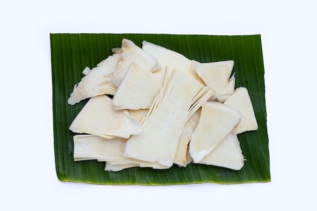 Germogli di bambù crudi affettati su foglia di banana su sfondo bianco.