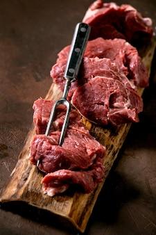 Carne di filetto di manzo crudo affettato per bistecche su tavola di legno con forchetta di carne in metallo, sale e pepe su sfondo marrone scuro. il cibo cucina il concetto di sfondo. avvicinamento
