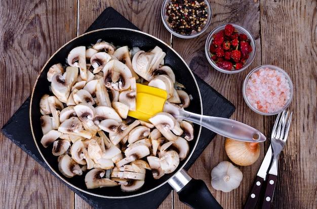 Fette di champignon crudi in padella sulla tavola di legno.