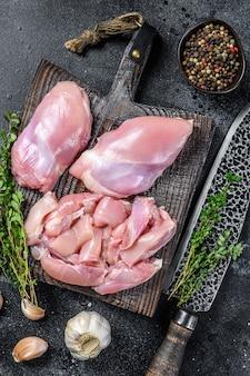 Filetto di coscia di pollo crudo affettato su un tagliere di legno.
