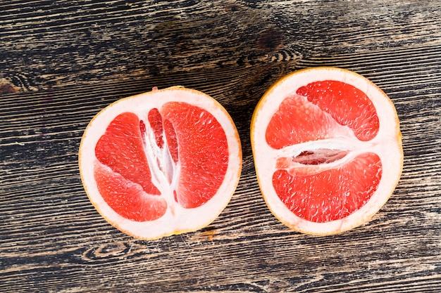 Pompelmo rosso a fette su una tavola nera, close-up di agrumi succosi e deliziosi