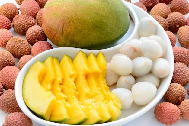 Manghi maturi affettati circondati dai frutti maturi del litchi su un piatto su un fondo bianco. litchi maturo senza guscio.