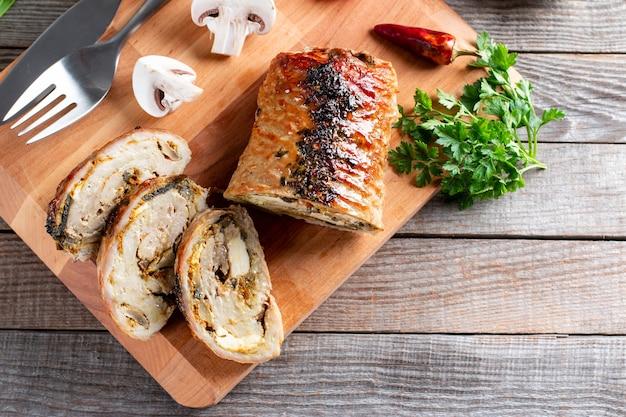 Fette di arrosto di maiale involtino - porchetta, servita su un tavolo di legno, close-up, flatlay, spazio di copia