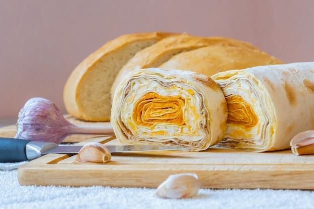 Rotolo di pane pita armeno a fette con ripieno di carote su una tavola di legno
